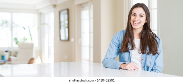 Wide angle picture of beautiful young woman sitting on white table at home with a happy and cool smile on face. Lucky person.