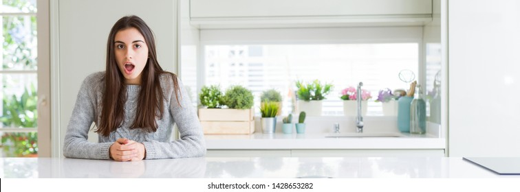 Wide angle picture of beautiful young woman sitting on white table at home afraid and shocked with surprise expression, fear and excited face.