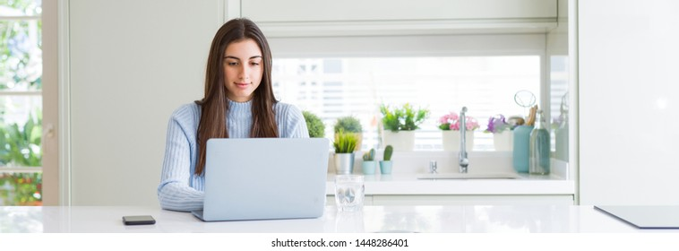 Wide angle picture of beautiful young woman working or studying using laptop with a confident expression on smart face thinking serious
