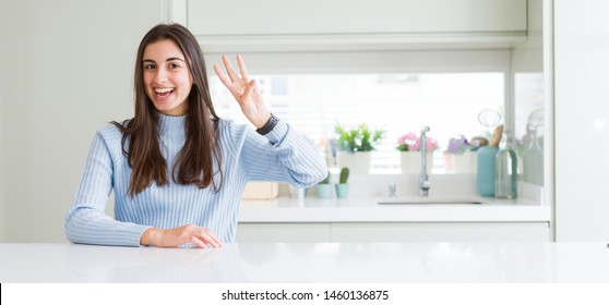 Wide angle picture of beautiful young woman sitting on white table at home showing and pointing up with fingers number three while smiling confident and happy.