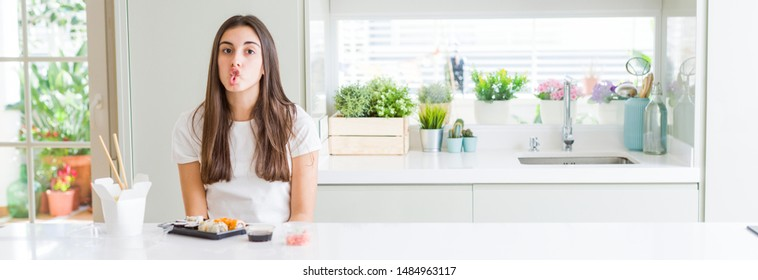 Wide angle picture of beautiful young woman eating asian sushi from delivery making fish face with lips, crazy and comical gesture. Funny expression.