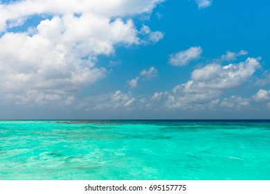 Wide angle picture from the boat of turquoise water at Maafushi during a sunny day with blue sky, Maldives.