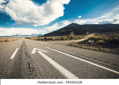Wide angle picture of driving on an empty road through the beautiful landscape at sunny day. Concept vision for a new beginning with a sign start and an arrow towards the sun.