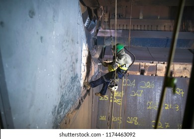 Wide angle picture of rope access sandblaster worker wearing safety equipment harness working at height abseiling on twin ropes commencing sandblasting in confined space construction site Perth, Aust