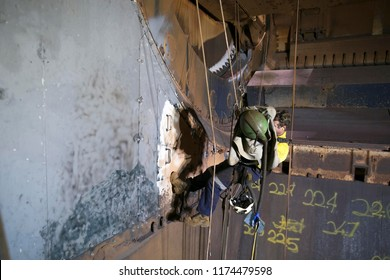 Wide angle picture of rope access sandblaster working at height abseiling on twin ropes wearing safety harness sandblast helmet before commencing sandblast confined space construction site, Australia