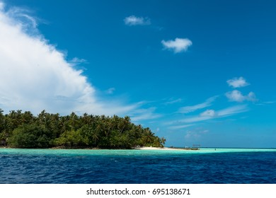 Wide angle picture of small island with many coconut trees closed to Maafushi in Maldives. Sunny day with clouds and blue sky.