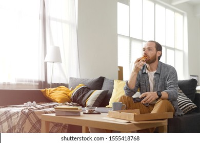 Wide angle portrait of bearded man eating pizza while watching TV at home in bachelors pad, copy space