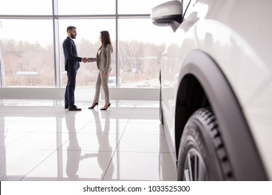 Wide angle portrait of car salesman shaking hands with woman buying new car in dealership showroom, car wheel in foreground, copy space