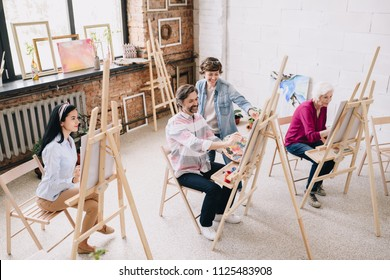 Wide angle portrait of female art teacher working with group of students painting at easels in spacious sunlit art studio, copy space