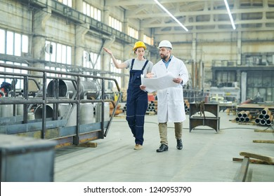 Wide angle portrait of female factory worker discussing plans with mature engineer walking  in workshop, copy space