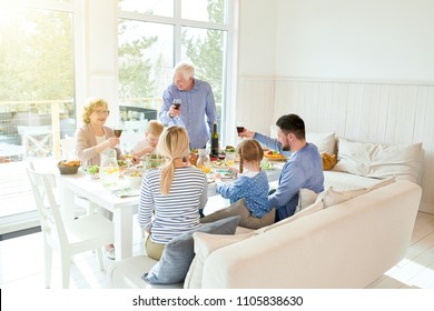 Wide angle portrait of happy two generation family enjoying dinner together sitting at festive table with delicious dishes and raising glasses during holiday celebration , copy space