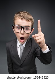 Wide angle portrait of little businessmen in spectacles forefinger gesturing, on grey background. Concept of leadership and success