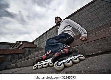 Wide angle portrait of a serious rollerskating man