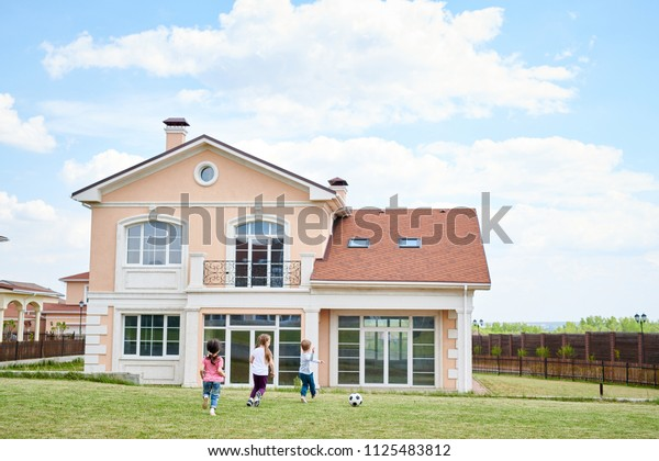 Wide angle portrait of three happy little kids playing football in front yard of beautiful two storey house, copy space