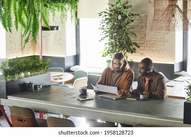 Wide angle portrait of two contemporary men collaborating on project during business meeting in green office or cafe interior, copy space
