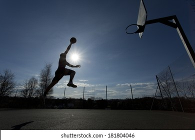 Wide angle shot of a basketball player silhouette taking off towards slam dunking the ball