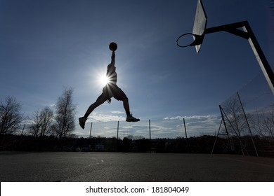 Wide angle shot of a basketball player silhouette in mid air about to slam dunk the ball with the sun creating a flare effect