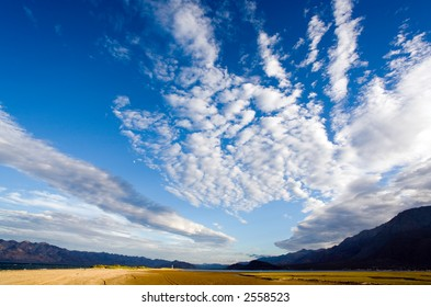 Wide angle shot of a blue sky and distant mountains with coastal marshes in the foreground.