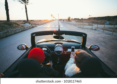 Wide angle shot of couple of teenagers or fashion internet influencers drive in cabriolet convertible mini car into sunset on palm alley. Teenage dream, forever young and happiness concept in summer