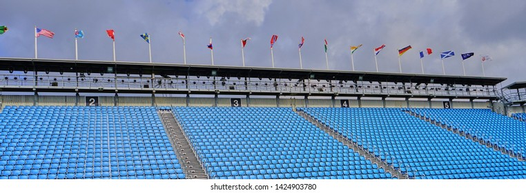Wide angle shot of empty blue bleacher seats in a large stadium.