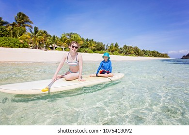 wide angle shot of family of two, mother and son, enjoying stand up paddleboarding in beautiful turquoise lagoon at fiji island, active vacation concept