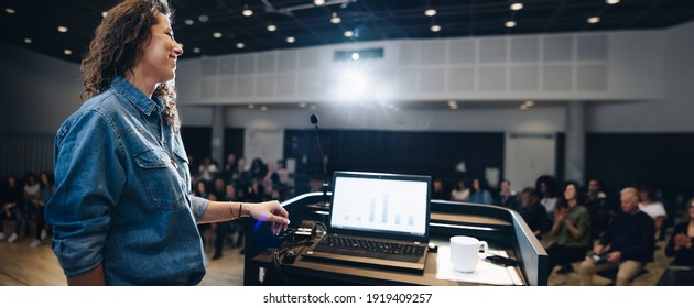 Wide angle shot of a female speaker standing at podium with laptop on the lectern and people sitting in the auditorium. Businesswoman giving a presentation in a corporate event.
