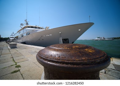 Wide angle shot of harbour close-up of mooring bollard with berthed vessel and sea in the background. Venice, Italy.