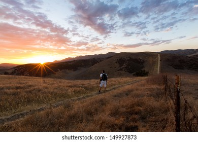 Wide angle shot of a hiker wearing a black backpack in the Santa Monica Mountains looking at a beautiful sunset
