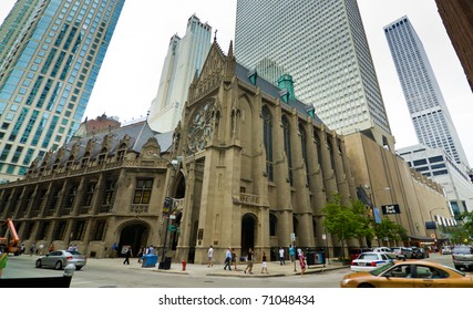 Wide angle shot of the Holy Name Cathedral and street in Chicago surrounded by modern skyscrapers.