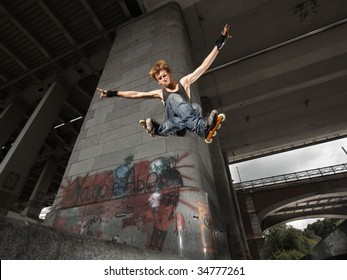 Wide angle shot of a jumping rollerskater on a dark urban background - with just a little motion blur