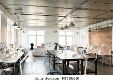 Wide angle shot of modern atelier interior with wooden workstation in foreground and sewing dummies, no people, copy space background