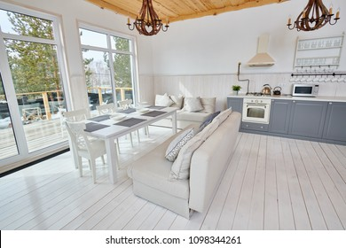 Wide angle shot of modern open living room interior overlooking floor to ceiling windows with white wooden table and grey kitchen counters in minimalistic Scandinavian design by sunlight, copy space