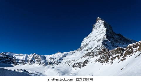 A wide angle shot of the north face of the world famous Matterhorn,  surrounding rock formations and glacier, on a very clear winter day close to Zermatt in Wallis in the Swiss Alps.
