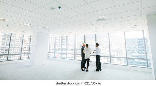 Wide angle shot of real estate agent with potential clients inside an empty office space. Estate broker showing new office space to business people.