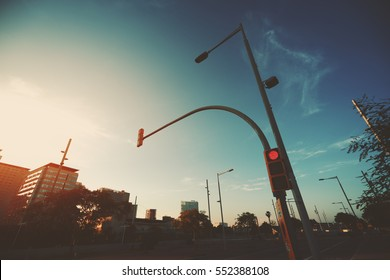 Wide angle shot of red traffic light on street lantern near highway, sunset and evening in residential Forum district of Barcelona, Spain, clear sky and distant spindrift clouds