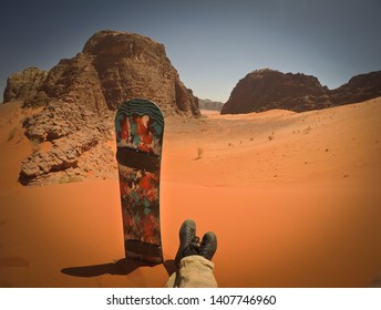 Wide angle shot with sandboard placed into sand dune, laynig young rider man with legs crossed with rocky desert area around, Wadi Rum, Jordan