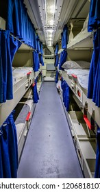 A wide angle shot of the tight quarters of a berthing compartment of a ship.