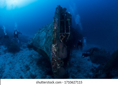 Wide angle shot of the Tuna Shipwreck in Thailands Andaman Sea with divers swimming around the sunken vessel. A truly amazing dive with super clear blue water.