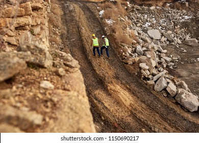 Wide angle shot of two industrial  workers wearing reflective jackets walking in dirt on mining worksite, copy space