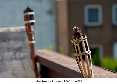 A wide angle shot of two unlit tiki torches next to each other on a building
