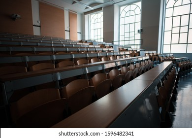 Wide angle shot of a university classroom with rows of chairs and desks
