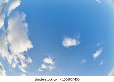 Wide angle shot with white clouds at the blue sky.