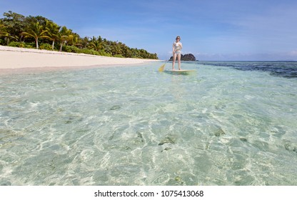 wide angle shot of young woman enjoying stand up paddleboarding in gorgeous lagoon at fiji island, active healthy vacation concept
