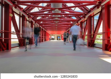 A Wide Angle Shutter Drag Shot of Pedestrians Blurring Through a Red Patterned Skyway in Downtown Minneapolis