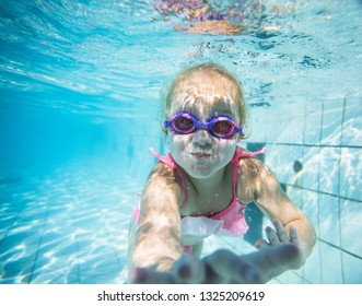 Wide angle underwater photo of a toddler girl swimming in a big swimming pool with goggles and a pink bikini