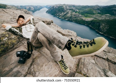 Wide angle unique portrait of traveler. Young man relaxing on stones in Norway. Guy sleeping outdoor. Pulplit rock landscape. Unusual odd person lying at edge of mountain with fjords on background
