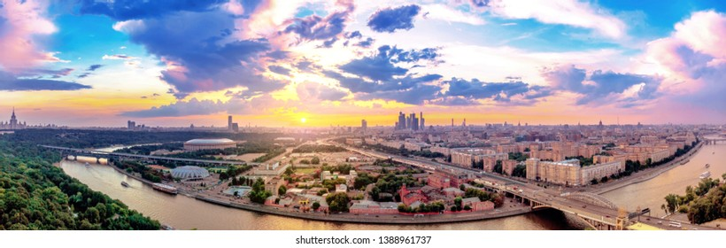 Wide angle vibrant panoramic view of sunset above Moscow wth cloud reflections in city river, traveling boats and bridge