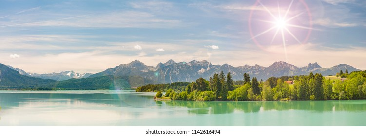 wide angle view to alps mountain range mirroring in lake Forggensee in region Allgaeu in Bavaria