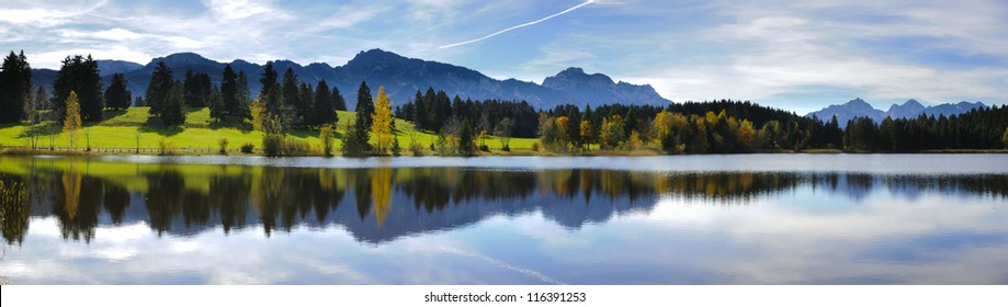 wide angle view to alps mountains mirroring in lake Forggensee in region Allgaeu in Bavaria, Germany