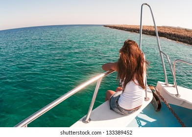 Wide angle view of back sitting woman on shipboard with legs out. Copyspace